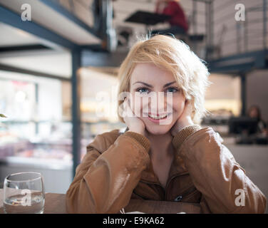 Portrait of beautiful young woman smiling in cafe - Stock Photo