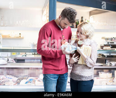 Young couple discussing over product outside cafe - Stock Photo
