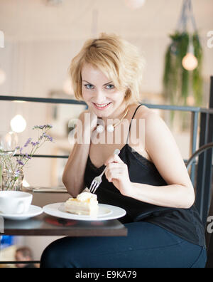 Portrait of happy young woman eating cake at cafe - Stock Photo