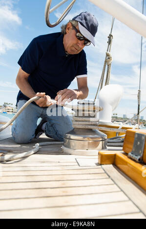 Middle-aged man winching rope on yacht - Stock Photo