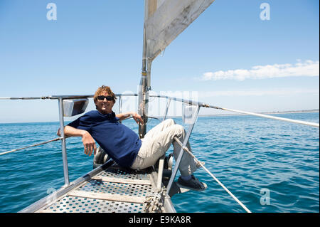 Full-length of happy man sitting on bow of yacht - Stock Photo