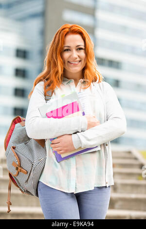 Portrait of beautiful student with textbooks at college campus - Stock Photo