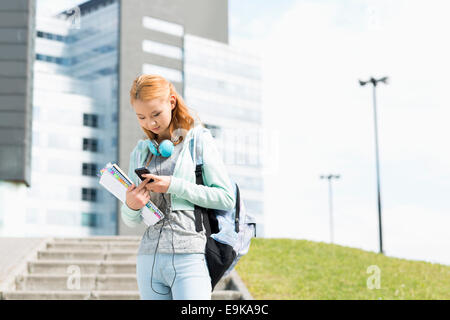 Young woman using smart phone at college campus - Stock Photo