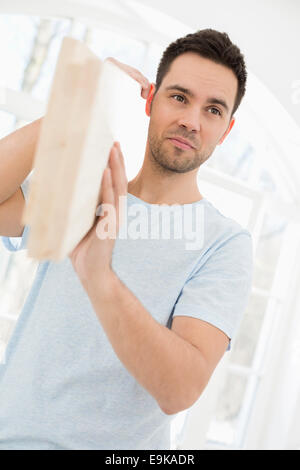 Mid-adult man carrying wooden plank on shoulder - Stock Photo