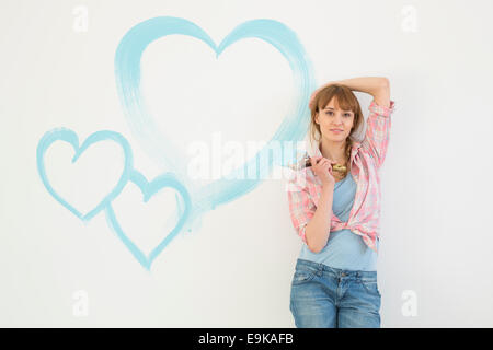 Portrait of beautiful woman holding paint brush with hearts painted on wall - Stock Photo