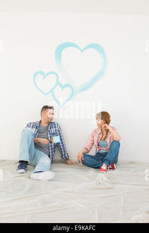 Full-length of mid-adult couple with painted hearts on wall - Stock Photo