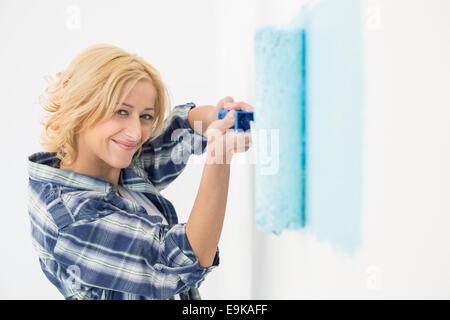 Portrait of beautiful woman painting wall with paint roller - Stock Photo