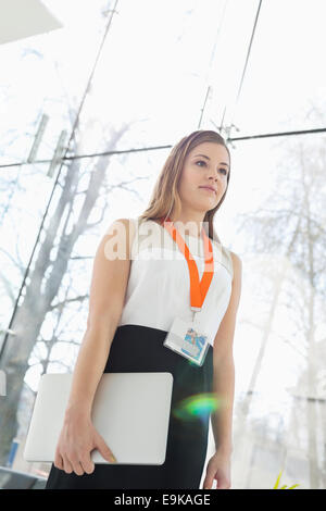 Beautiful businesswoman holding laptop by glass wall in office - Stock Photo