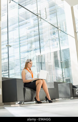 Young businesswoman using laptop at office lobby - Stock Photo
