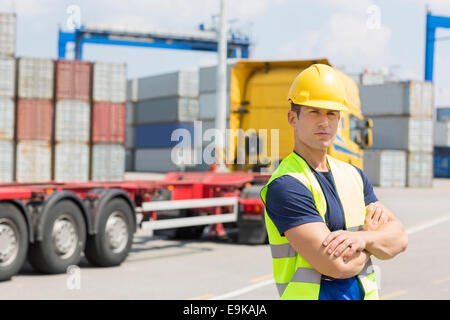 Portrait of confident mid adult man in shipping yard - Stock Photo