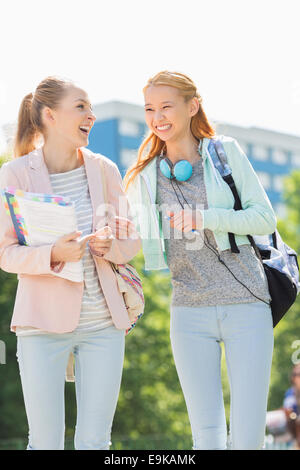 Cheerful young female college students walking in campus - Stock Photo