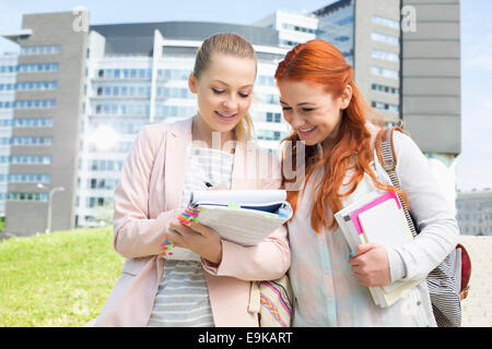 Happy young female college students studying in park with building in background - Stock Photo