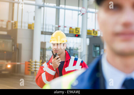Male worker using walkie-talkie with colleague in foreground at shipyard - Stock Photo