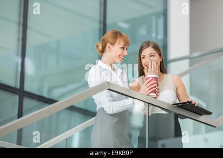 Businesswomen gossiping while having coffee on steps in office - Stock Photo