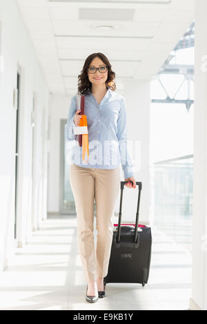 Portrait of confident businesswoman with luggage at airport - Stock Photo