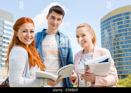 Portrait of happy young university students studying outdoors - Stock Photo