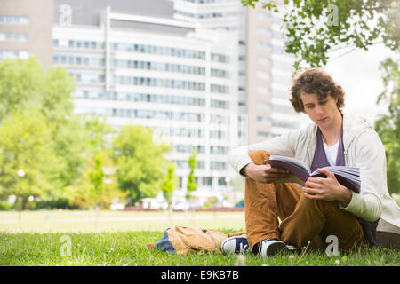 Full length of young man reading book on college campus - Stock Photo