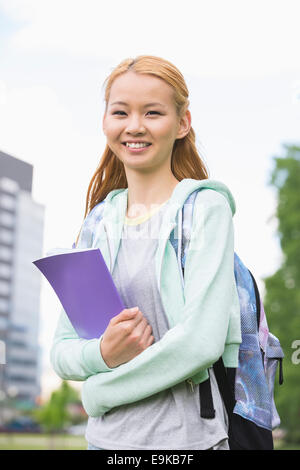 Portrait of happy young woman holding book at college campus - Stock Photo
