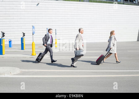 Side view of businesspeople with luggage walking on street - Stock Photo