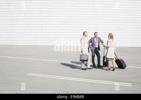 Businesspeople with luggage communicating on street - Stock Photo