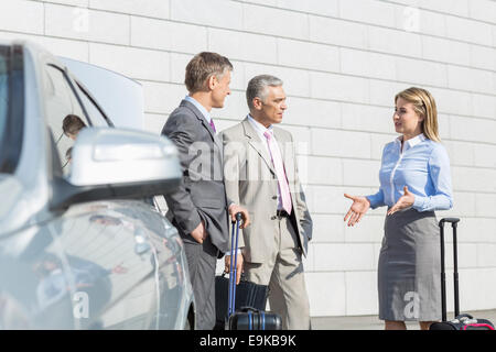 Businesspeople with luggage discussing outside car - Stock Photo