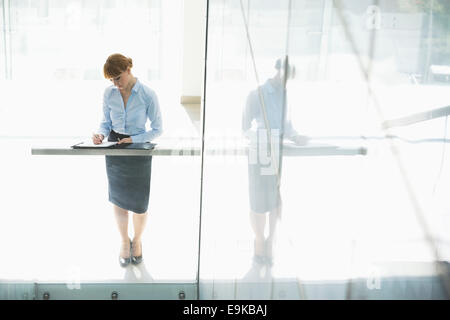 Full-length of businesswoman writing on document in office - Stock Photo