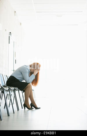 Side view of frustrated businesswoman sitting on chair in office - Stock Photo