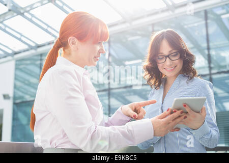 Businesswoman showing something on tablet PC to colleague in office - Stock Photo