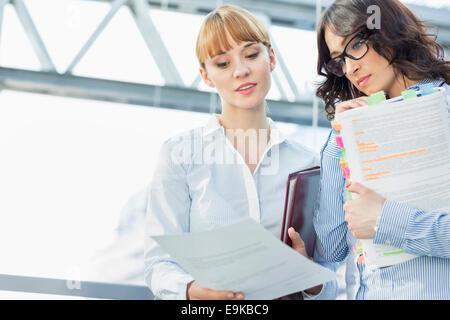 Businesswomen reading document in office - Stock Photo