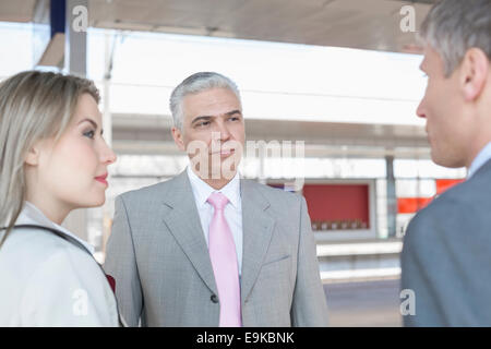 Businessman with colleagues on train platform - Stock Photo