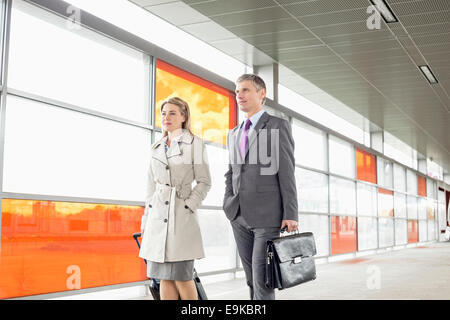 Businesspeople with luggage walking in railroad station - Stock Photo