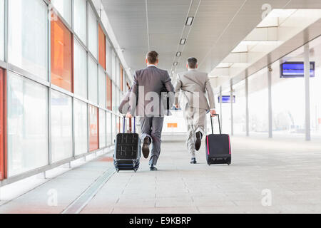 Full length rear view of businessmen with luggage running on railroad platform - Stock Photo