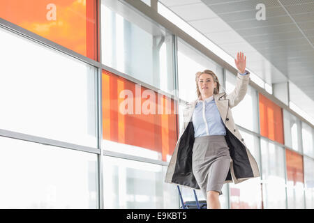 Young businesswoman with luggage running in railroad station - Stock Photo