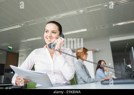 Smiling young businesswoman holding documents while using landline phone with colleagues in background at office - Stock Photo