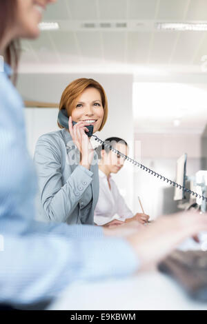 Smiling young businesswoman using landline phone in office - Stock Photo