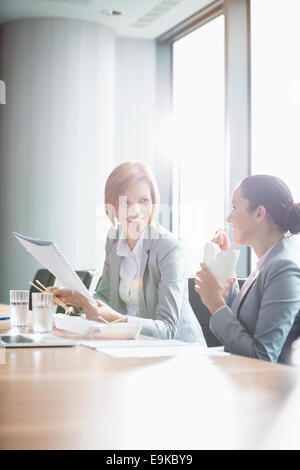 Young businesswomen working while having lunch at table in office - Stock Photo