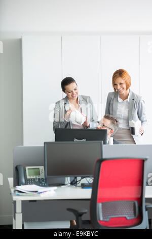 Business people having lunch while using computer in office - Stock Photo