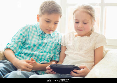 Siblings playing hand-held video game at home - Stock Photo