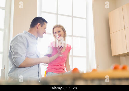 Happy couple drinking red wine in kitchen - Stock Photo
