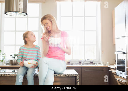 Happy mother and daughter having breakfast in kitchen - Stock Photo
