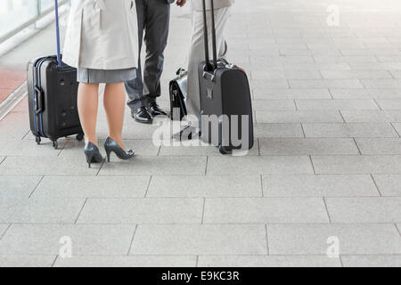 Low section of businesspeople with luggage standing on railroad platform - Stock Photo