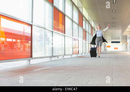 Full length of young businesswoman with luggage rushing in railroad station - Stock Photo