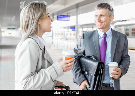 Businessman and businesswoman with coffee cups talking at railroad platform - Stock Photo