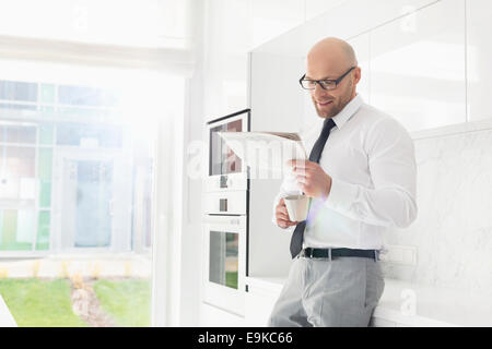 Mid adult businessman having coffee while reading newspaper at home - Stock Photo