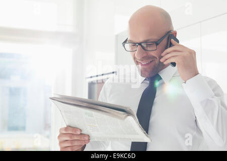 Happy businessman on call while reading newspaper at home - Stock Photo