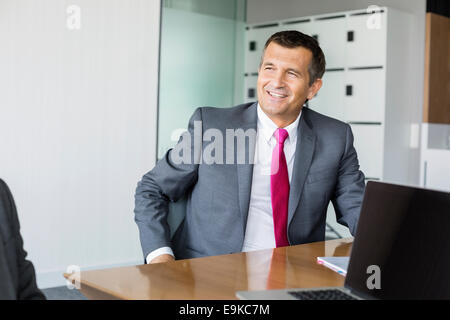 Happy mature businessman sitting at desk in office - Stock Photo