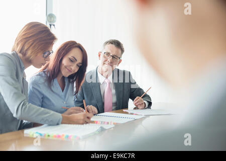Business people working together at conference table - Stock Photo