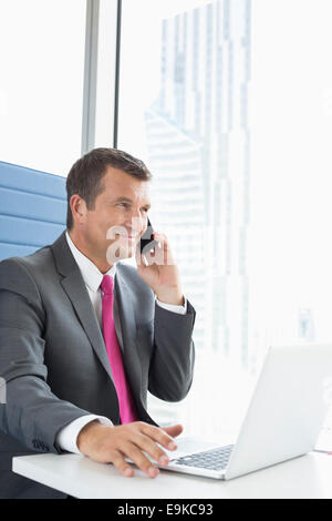 Mature businessman talking on cell phone while using laptop in office - Stock Photo