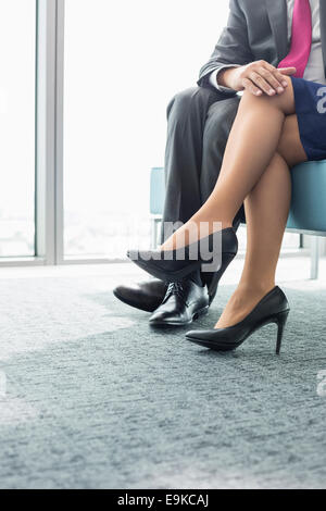 Low section of businessman flirting with female colleague in office - Stock Photo