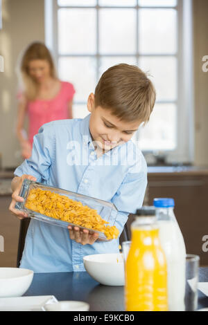 Boy pouring corn flakes in bowl with mother standing in background - Stock Photo